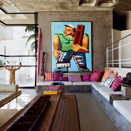 Un salon exotique hétéroclite  Au milieu de murs bétonnés, le salon exotique se compose d'un mobilier aux teintes sobres, créant une harmonique parfaite. Le tout est rehaussé de touches de couleurs pour égayer la pièce et accentuer le style exotique du lieu qui invite au voyage.      Pour en savoir plus : Un salon exotique hétéroclite - Marie Claire Maison