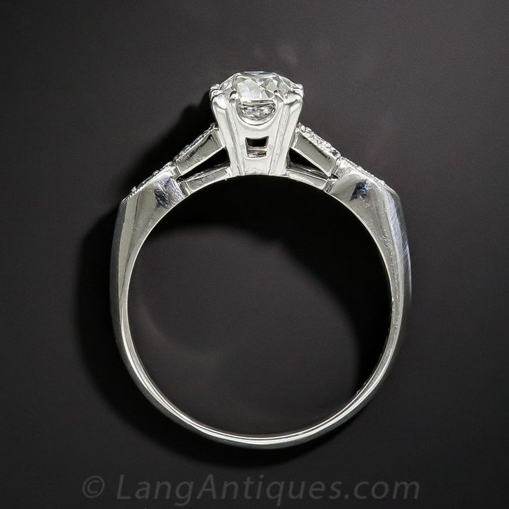 Dating back from the early 1940s thru the early 1950s, this classic solitaire engagement ring highlights a bright-white and shining, high-quality, transitional European-cut diamond, weighing .89 carats. The scintillating stone sparkles between sleekly designed shoulders, each set with a pair of small round diamonds: one set in a square setting, followed by a navette shape setting, and leading in turn to a soft knife-edge ring shank. A timeless vintage jewel, accompanied by a GIA Diamond…