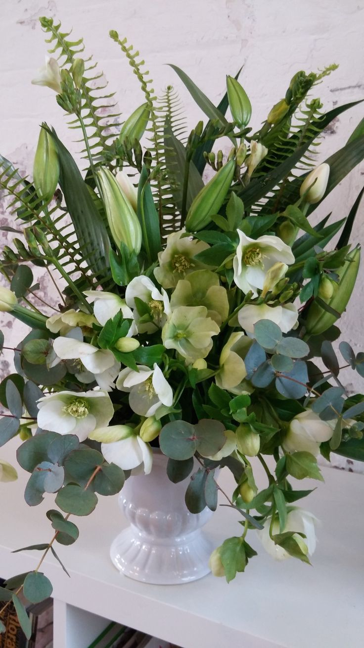 SMALL URN arrangement featuring lilies, fishbone fern, hellebores, tulips and eucalyptus.