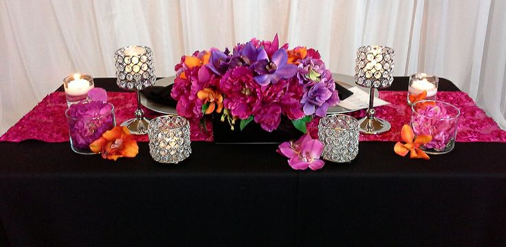 bridal table setting with rich purples, pink, orange and crystal candle holders; design by Davis Floral Creations