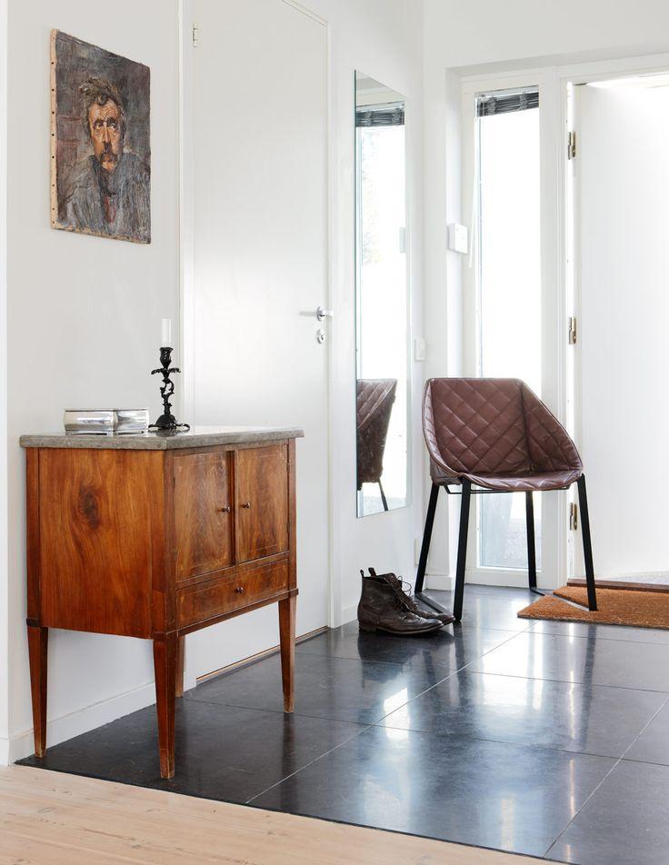 I entrén ligger ett vackert kalkstensgolv. Det lilla skåpet med marmorskiva är ett auktionsfynd. Skinnstol från holländska designern Piet Boon.
