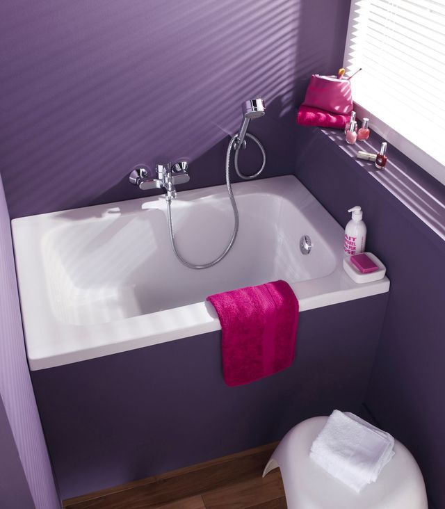 Une salle bain prune avec mini baignoire sabot.