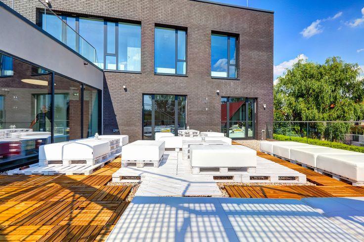Sundeck Digital Knowlagde Villige to ponad 100m2 patio, które idealnie sprawdzi się jako miejsce odpoczynku i relaksu w przerwie od pracy. Znajdujące się na tarasiewygodne, jasne kanapy istoliki w połączeniu z zielenią okolicy tworzą niezobowiązującą atmosferę pozwalają na chwilę wytchnienia.