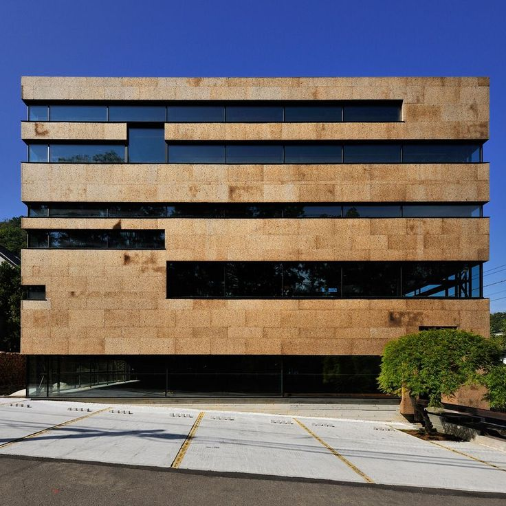 Strip windows create horizontal stripes across the facade of this office in…