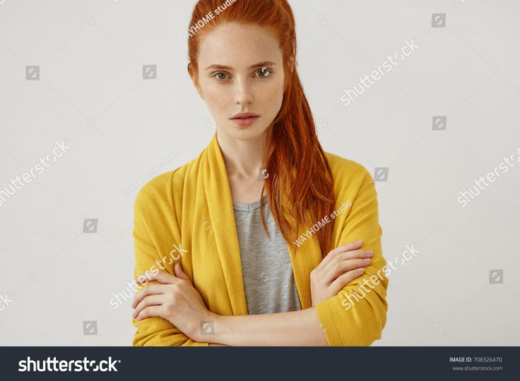 Attractive female with reddish pony tail, standing crossed hands feeling self-assuarance while posing against blank studio wall. Confident freckled female model isolated over white background