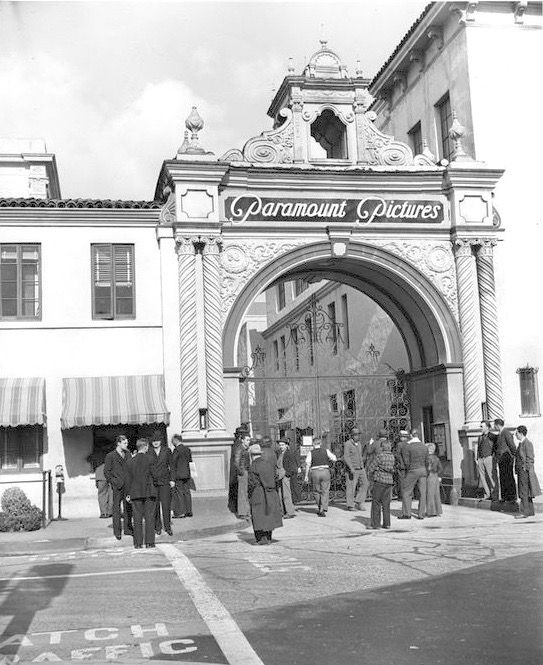 """I imagine this was a pretty common scene outside Paramount during the 1930s – people lingering outside the studio gates in the hopes that they might be hired as extras or something. I wonder how many of these people actually found themselves on the set of some picture. This photo was taken in 1939 aka """"Hollywood's Greatest Year"""" so maybe some of these guys ended up as French Foreign Legionaries in """"Beau Geste."""""""