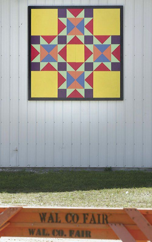 The County Fair quilt hangs on a barn at the ...