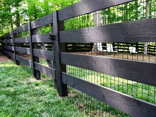 Rustic 4-board fence stained black, with black vinyl welded wire: