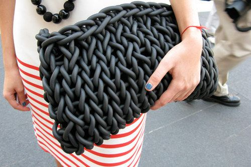 knitted clutch, I think from neopren. (could make shopping bags by knitting plarn from old plastic bags)