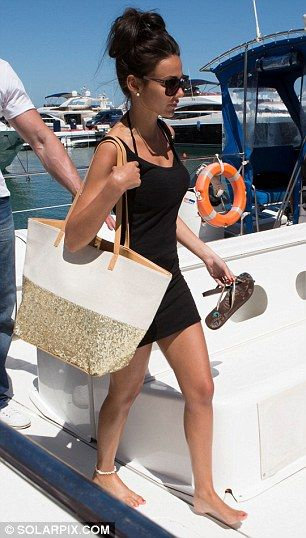 All aboard: The former Coronation Street actress removes her flip flops as she climbs onto the party boat chartered to ferry them across the picturesque harbour
