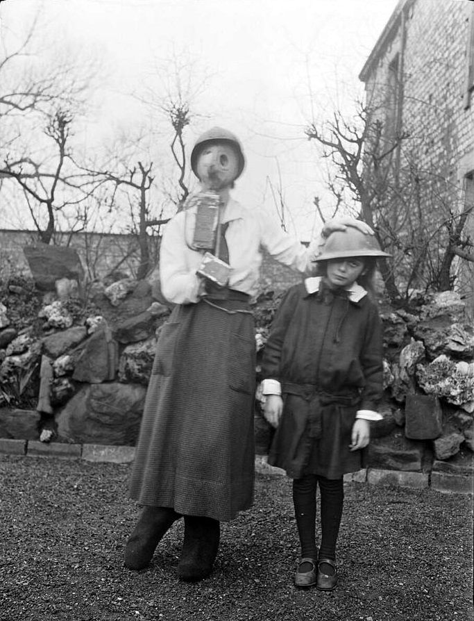 Michael Terry's sisters Frances and Charlotte wearing his Russian gas mask and tin hat, Benwell, England, December 1918 / Michael Terry