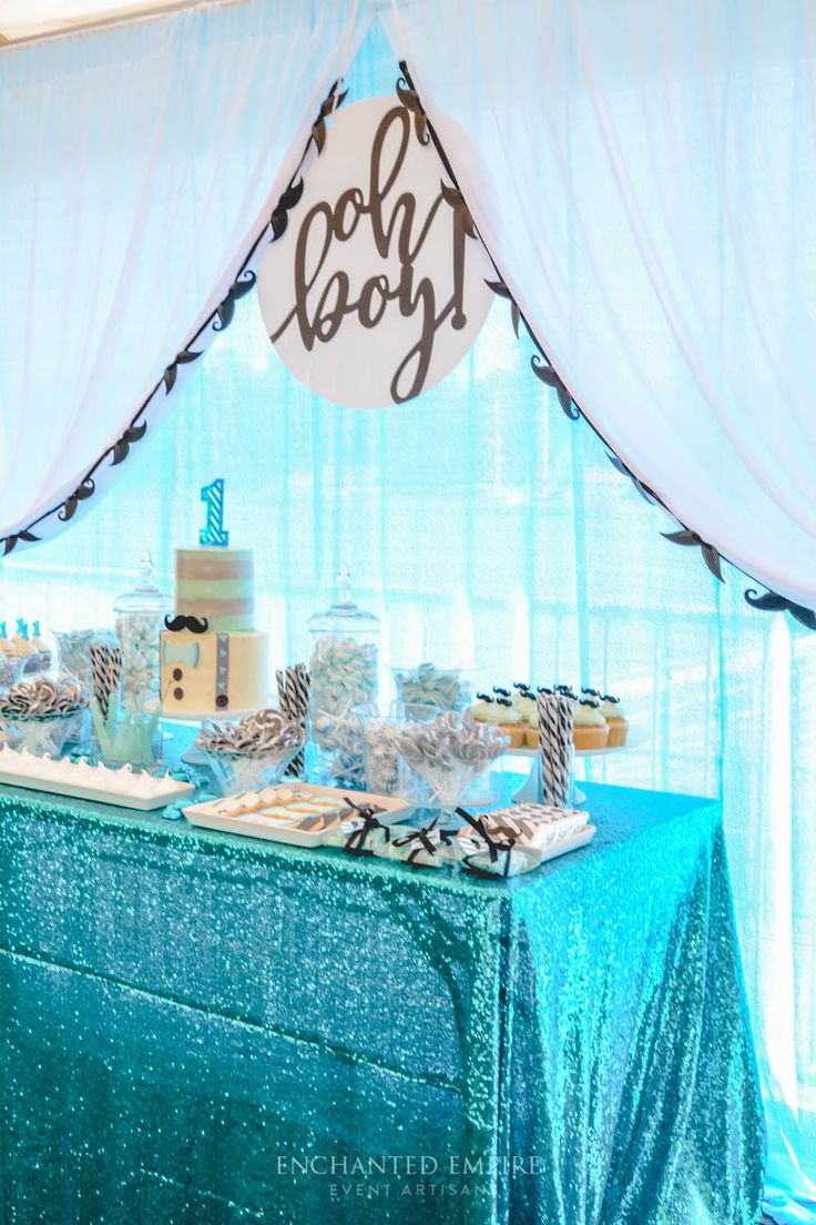 Little Man Moustache birthday party styled with a fresh colour palette consisting of a grey base and turquoise, accented by black moustache graphics and 'oh boy' signage. Crisp white florals, grey and dusk blue geo vases and moustache napkin rings complimented turquoise napkins and silver plates. A bright candy station with custom wrapped chocolate bars and labelled gift bags created a vibrant theme across the sweets table. See our full film on our You Tube Channel…