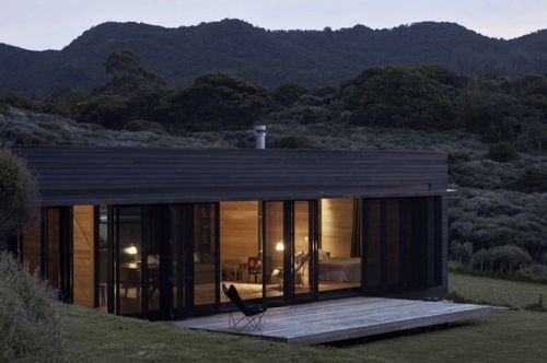 12 Modern House with Black Exteriors: Storm Cottage by Fearon Hay Architects is located on the east coast of Great Barrier Island in New Zealand. The black rough sawn timber box sits looking north to the sea. A slice of heaven.