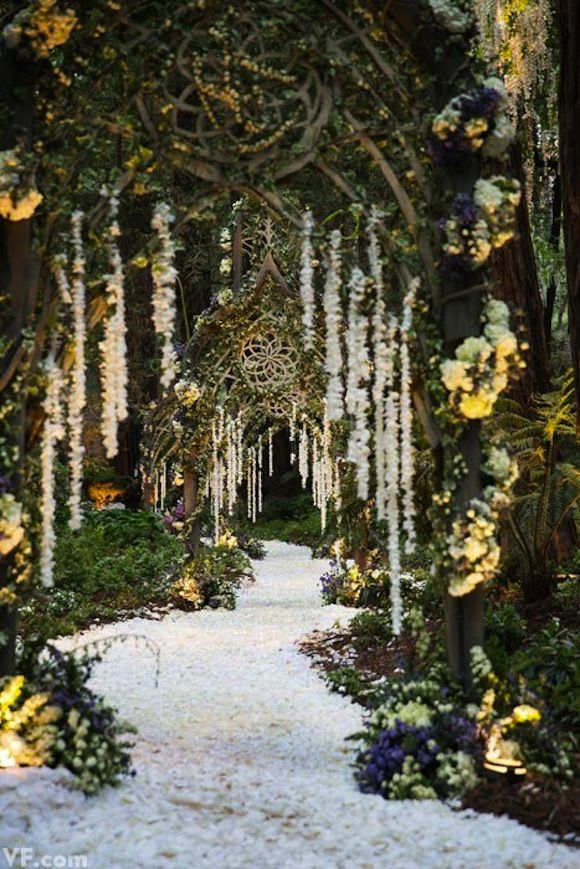 hanging floral garland and a decorated path create this fairytale-like entrance way/Preston Bailey