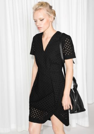 All-over geometric broderie anglaise merges romantic quality with sharp tailoring in this figure-tracing V-neck dress finished with a wrap skirt.