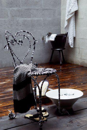 Une chaise en fer forgé recouverte de rubans en coton noir et blanc noués