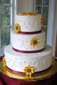 Three tier round white wedding cake decorated with yellow sunflowers. (WOULD USE DIFFERENT COLOR FLOWERS & RIBBON)
