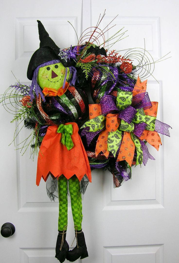 A cute little scarecrow burlap and felt witch with multi colored stripe deco mesh in orange, green, purple and black. There are glittered picks with pumpkins, a spider, and bat. A twelve loop bow with