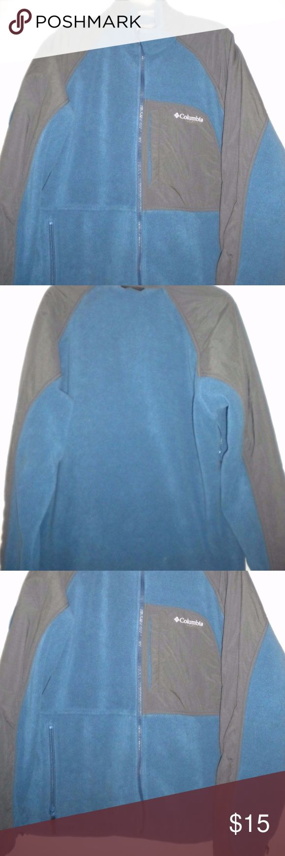 Columbia Men Large Fleece Vertex Core Jacket Gently Worn.  Columbia Men Size Large Jacket. Long Sleeves.  Zipper front.  Two front zip pockets. Blue and charcoal. Fleece and nylon pattern. Vertex.  Core.  Interchange.   Adjustable elastic along the bottom.  Snap chest pocket. Zipper under the arms. Made of Polyester and Nylon. Chest approximately 54 inches and length approximately 27 inches in front and 30 inches in back. TUnder shoulder seam to end of cuff approximately 23 inches.  Back…