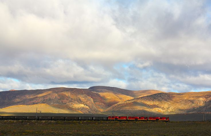 This country, beauty to behold.A red train brings colour to the evening light somewhere near Matjiesfontein. Shot from Hein van Tonder's moving car as we took to a Karoo road trip and renewed our appreciation for South Africa.
