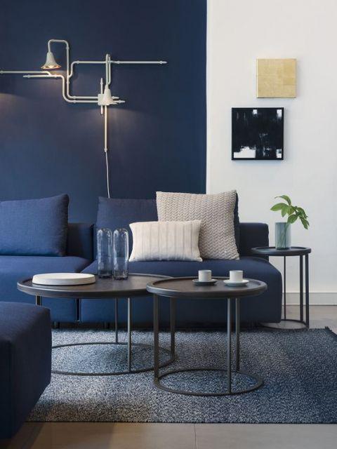 Sala de estar com sofá azul escuro e almofadas claras.