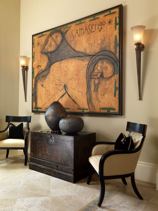 Part of a great room - warm colour palette and dark espresso furnishings & decor with 2 torch wall sconces flanking a large art work.
