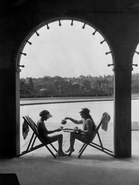 1935: Two women wearing swimming costumes and sun visors have a cup of tea under an archway at Finchley swimming baths.