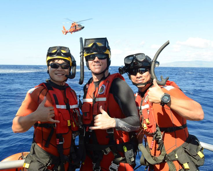 Senior Chief Petty Officer Jeremy Carroll, an aviation survival technician from Air Station Barbers Point, stands with Korean coast guard rescue swimmers after conducting training off Oahu, Hawaii.