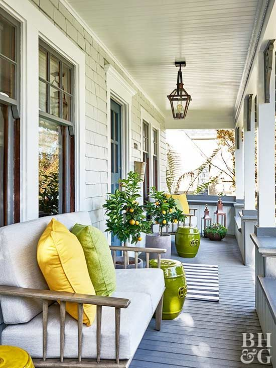 Porch ideas for summer don't have to be complicated. Sometimes a simple swap of color palette can make your design feel fresh again. With a neutral base of gray and beige, it's easy to inject little pops of color, like the citrus tones of lemon and lime featured on this seating of this summer porch.
