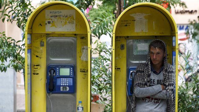 Seorang pengungsi Afghanistan berlindung di bilik telpon di tengah hujan lebat di Lapangan Victoria, Athena, Yunani. Ratusan migran dan pengungsi terpaksa bermalam di sana.