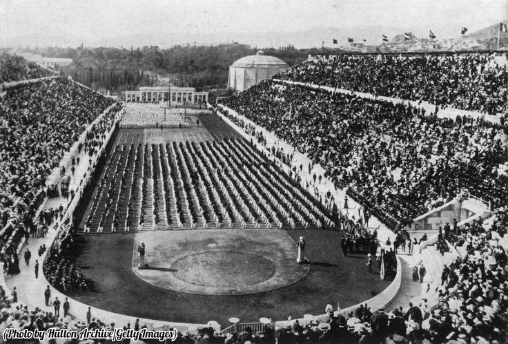 Athletes standing in rows and crowds filling the stadium at the first Modern Olympics in Athens, Greece, 1896.