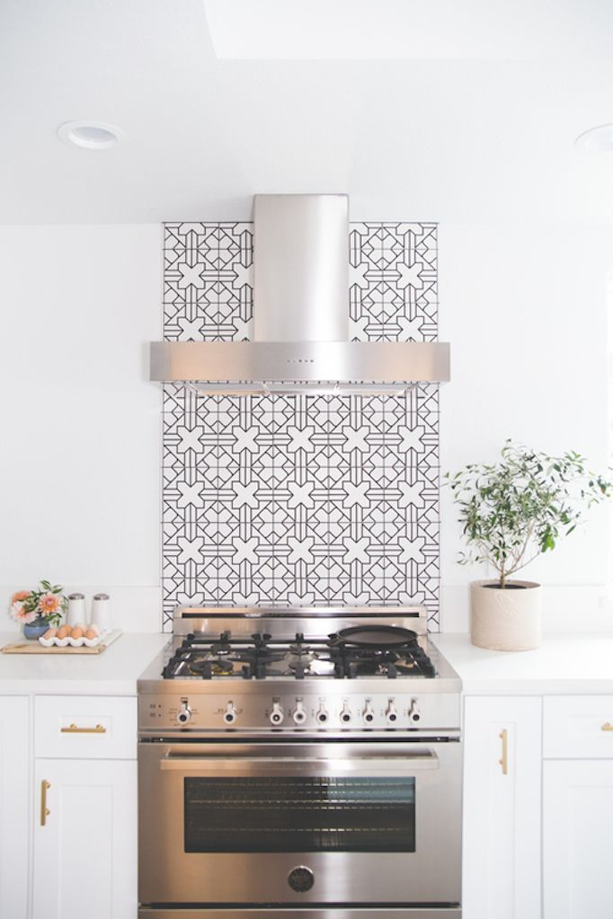 Unique kitchen featuring a steel hood, white cabinets, gold fixtures and Moroccan style tile behind the stove   Fireclay Tile