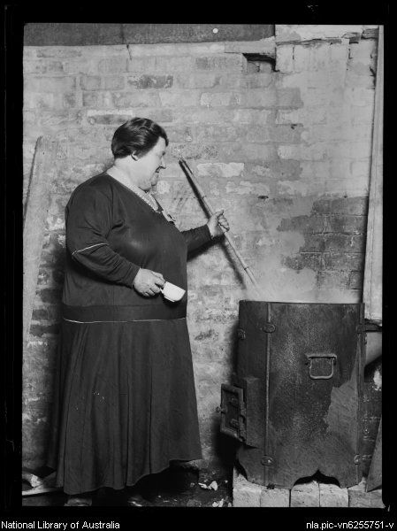 Woman stirring a metal pot at the Redfern Fish Markets during the Great Depression, Sydney, 29 May 1932
