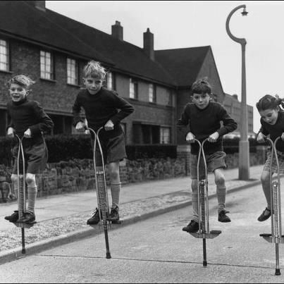 Kids bouncing along the road on their pogo sticks (1958)