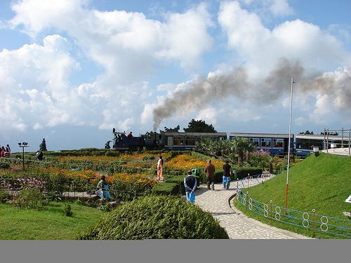 Toy Train at Batasia Loop- Batasia Loop & War Memorial, Darjeeling The sudden decrease in altitude and congested space makes it impossible to lengthen the track to cover the gradiant. Thus the track makes a loop and passes below itself in this loop.  Leaving Ghum the toy train descends towards Darjeeling. From the Batasia Loop you can get a spectacular view of Darjeeling town with the Kanchenjunga and other snowy mountains in the back-drop.