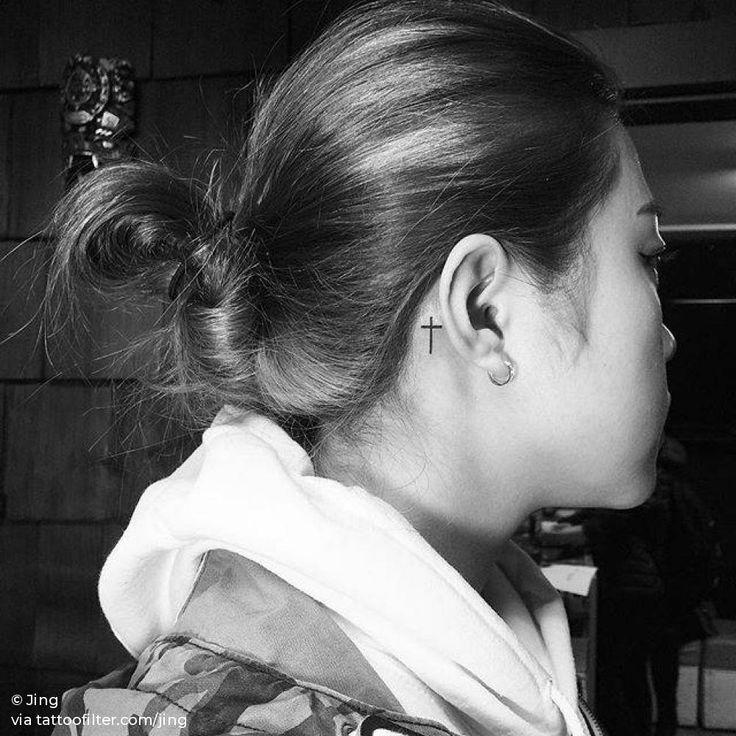 Minimalist cross tattoo behind the right ear.