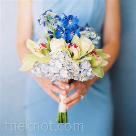 The blue hydrangeas and delphiniums matched the bridesmaid dresses, while green orchids provided a bright contrast.