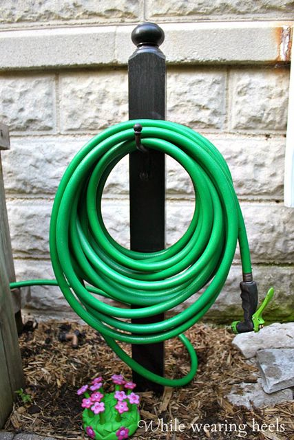 Corral your garden hose with a  DIY holder. This looks so much better than those ugly carts!