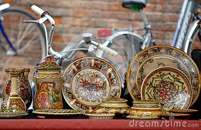 Photo made in the capital of the province Ferrara in Emilia-Romagna (Italy). In the photo taken at a stall during a market in the square next to the castle, above which you can see the ceramic plates colored hand-drawn by local artisans. Behind the decks you see the inevitable Ferrara bicycles being known as the city of the bicycle.