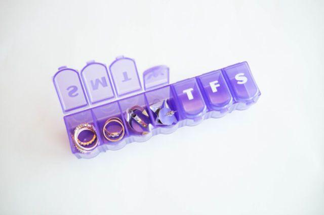 Gebruik een pillendoosje of een schoon lippenbalsemblikje om kleinere sieraden, zoals oorbellen en ringen, veilig en georganiseerd mee op reis te nemen.  -Cosmopolitan.nl