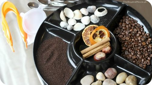 Sensory Play On A Mirror with coffee, shells and pebbles.
