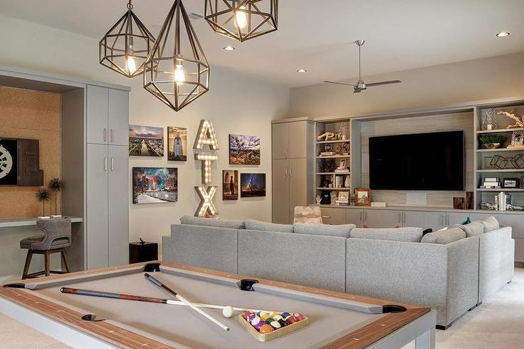 Staggered polyhedron pendants are hung over a pool table positioned behind a gray sectional facing a gray television unit fitted with gray cabinets and styled gray shelves flanking a flat panel television.