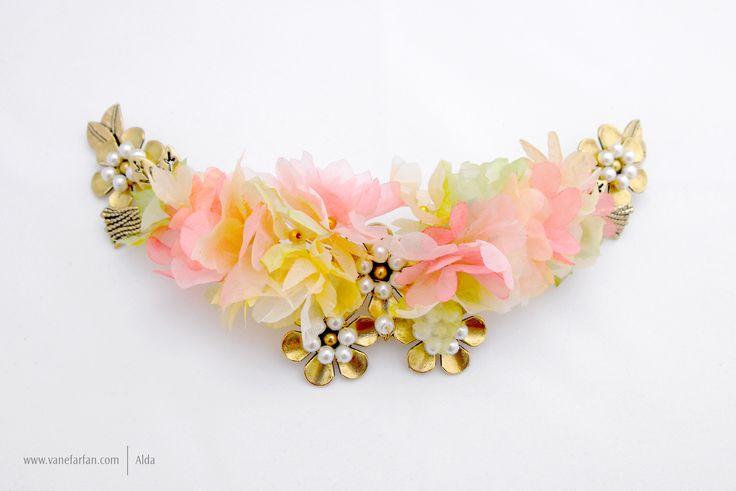Tocado elaborado en flores de gasa con apliques en color oro.