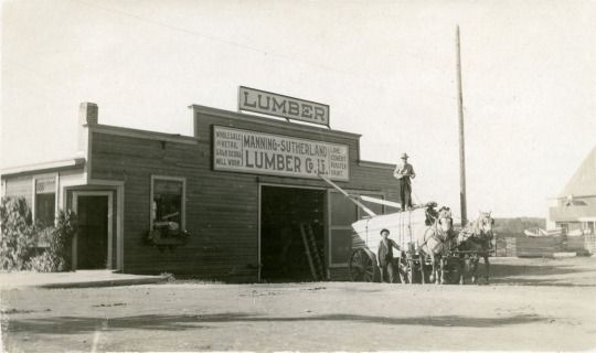 The Manning Sutherland Lumber Yard, c. 1925. It was located on the west side of Gaetz Avenue, south of 48th Street. The building on the right side of the photo is the original Sacred Heart Roman Catholic Church. Before the former church was torn down in the early 1960's, it was used as a paint storage building.