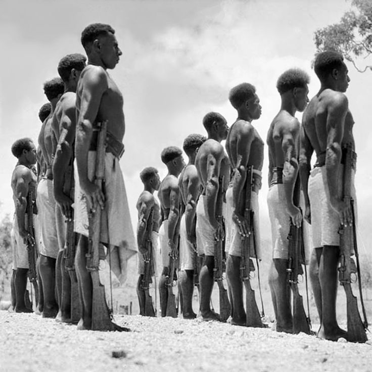 Papuan soldiers of the Papuan Infantry Battalion (PIB) are drilled at Port Moresby after the Battalion was raised on 27 May 1940 by the Australian Army to help combat the Japanese occupation of New Guinea. Port Moresby, Territory of Papua (now, Papua New Guinea). April 1941.