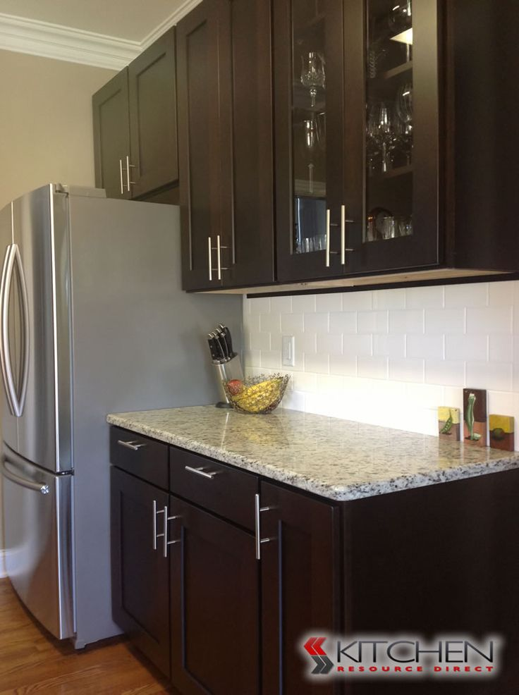 Shaker style cabinets in an Espresso finish with granite counter tops and white subway tile backsplash