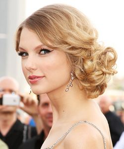 Prom updo on Taylor Swift, something between a side-bun and a ponytail with lots of curls (and lots of pins)