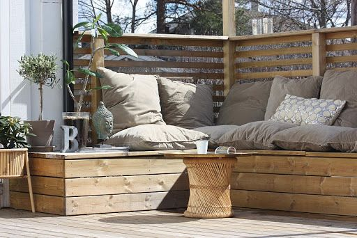 Corner seating with cushions in decked garden patio. Really nice!