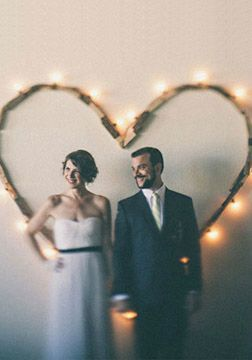 Decorate your wedding backdrop with a gorgeous wooden heart and romantic string lights for a beautiful rustic-chic look.