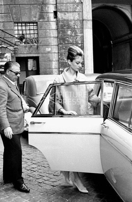 The actress Audrey Hepburn photographed by Elio Sorci in Rome (Italy), on March 16, 1961.  Audrey was wearing:  • Coat: Givenchy (of beige wool, single-breasted with two buttons of resin in the same color, collar à revers and sleeves with height above...